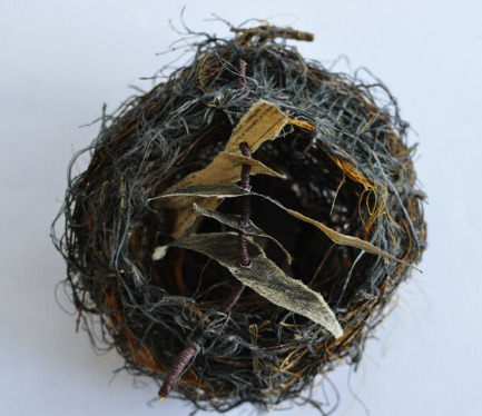 """65 / 1971 / Place of Safety / Sharon Hall Shipp / paper printed with the contents page of a 1971 issue of the magazine """"Family Circle"""", found synthetic string, darning wool, twigs and lavender sticks"""